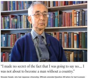 """Photo of an older Japanese American man with white hair, glasses, and wearing a light blue buttoned shirt, blue tie, and royal blue cardigan sweater, looking to the right of the camera, and sitting in front of a wall of multicolored books. Underneath the photo is the text, """"I made no secret of the fact that I was going to say no... I was not about to become a man without a country."""""""