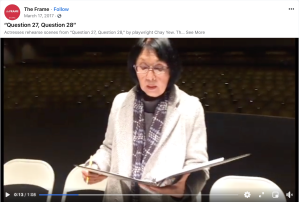 Screengrab of a video with an older Japanese American woman with fair skin, chin-length black hair, glasses, wearing a white jacket, holding a script in a binder, and standing on stage at the Aratani Theatre, with chairs behind her.