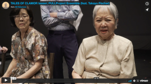 a screengrab of a video trailer, with a shot of two Japanese American women in dresses, sitting and looking towards the camera.
