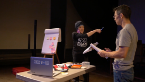 """Photo of two performers in discussion during rehearsal. Facing towards the camera is a Japanese American person wearing a black beanie and black shirt with """"By Any Means Necessary"""" is pointing to the right. Facing away from the camera is an Asian American man with short black hair, and wearing glasses and an olive shirt, holding a script. In between the two performers is a table with a silver notebook computer and scattered items. In the background in a giant notepad with multicolored post-its on an easel."""