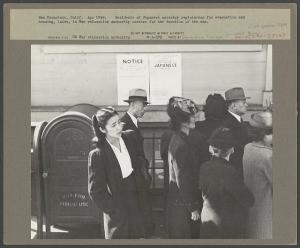 photo of a Japanese American woman in the 1940s, standing in a line, looking ahead. In the background, posted notices of Executive Order 9066.