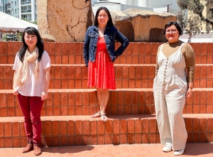 three women standing in the orange brick courtyard of the Japanese American Cultural and Community Center. Left to right: Julia Cho, Stefanie Lau and Marie-Reine Velez